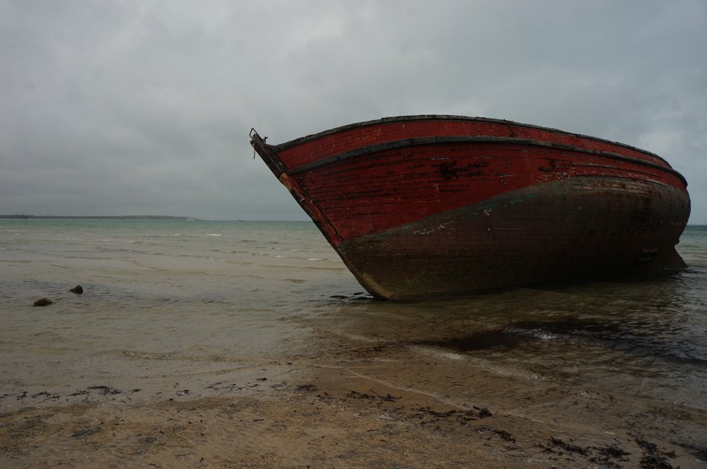 Lowtide boat resting on the beach in a cloudy day in Vilanculos.